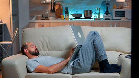 Man falling asleep in fron of TV while working on the laptop. Cozy man lying down on sofa while typing on laptop computer for social media project. Exhausted man working Foto de archivo