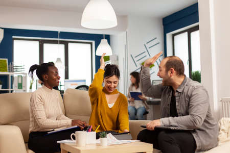 Diverse team of successful young entrepreneurs sharing high-five celebrating success sitting on couch in start up office room. Multiethnic business team with laptop and papers excited about project