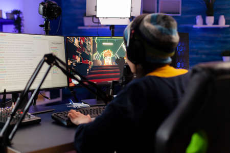 Pro woman gamer with headphone streaming videogames in gaming home studio. Professional player talking with other players online for game competition playing on powerful computer