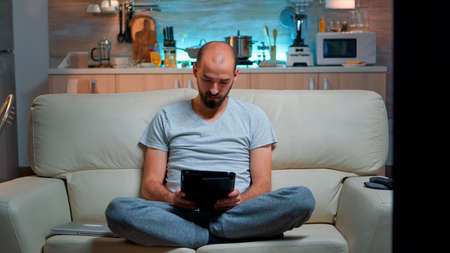 Tired man sitting alone on couch while browsing on internet using tablet computer with modern technology wireless. Caucasian male in pajamas relaxing in front of televion late at night in kitchen Foto de archivo