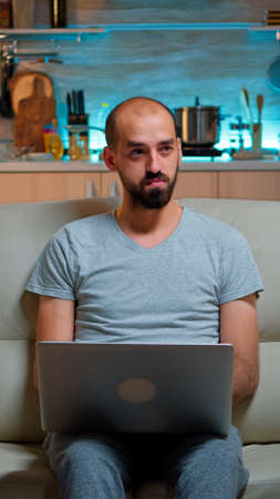 Focused man sitting on sofa and writing online project on laptop late at night in living room. Caucasian male working from home while watching tv, browsing on internet using network technology Foto de archivo