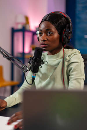 African influencer answering questions while talking into microphone for listeners. Speaking during livestreaming, blogger discussing in podcast wearing headphones.