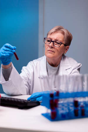 Biotechnologist senior doctor analysing a blood tube for medical investigation. Researcher in medicine lab working with professional technology equipment for diagnostics development and healthcare.