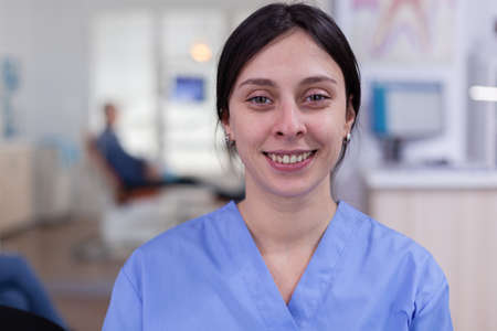 Dental assistant looking at camera while doctor examining patient in background. Professional stomatologist nurse smiling on webcam sitting on chair in waiting room of stomatological clinic.