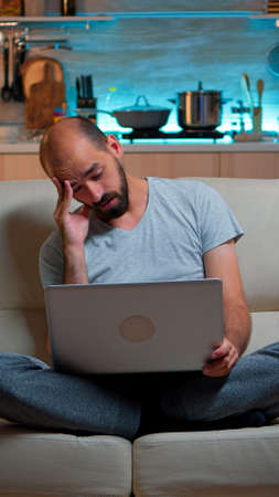 Tired man in pajams browsing on internet lifestyle information using laptop computer sitting on sofa. Freelancer working at online project in front on television late at night in kitchen