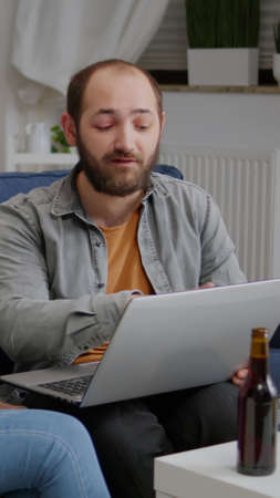 Multi-ethnic friends socializing while watching online funny videos on laptop resting on sofa. In background two womens drinking beer enjoying time spend together during entertainment party