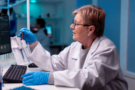 Scientist analysing blood test sample in medical facility hospital. Foto de archivo
