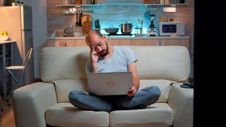 Tired man in pajams browsing on internet lifestyle information using laptop computer sitting on sofa. Freelancer working at online project in front on television late at night in kitchen Foto de archivo