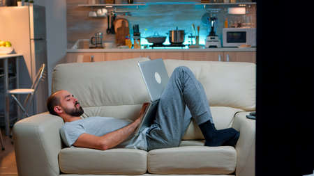 Exhausted man falling asleep while working on internet communication project using laptop computer with modern technology wireless. Caucasian male in pajamas sitting on sofa late at night in kitchen Foto de archivo