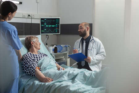 Doctor talking with elderly patient sitting next to bed in hospital room, giving expertise for treatment. Senior woman breathing with help from oxygen mask laying in bed.
