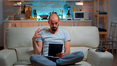 Focused man having online meeting videocall on tablet computer speaking using videoconference online web internet communication. Caucasian man browsing on internet for deadline project