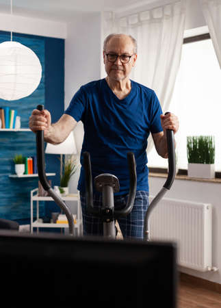 Active senior man training legs muscle resistance cycling bicycle machine in living room during lifestyle healthy workout. Pensioner watching fitness video on televison for well being