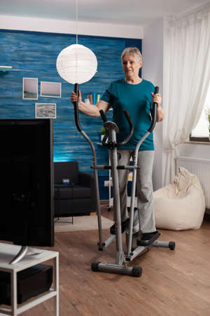 Focused senior woman working at legs muscle resistance cycling bicycle machine in living room during aerobics healthy workout. Pensioner watching fitness video on televison for well being
