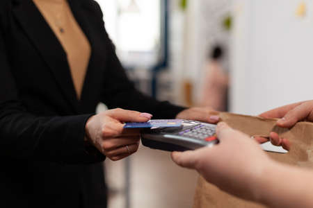 Close up of businesswoman holding plastic credit card in hand, paying for food delivery in company office. Using contactless pay for takeaway food. . Bringing tasty meal.