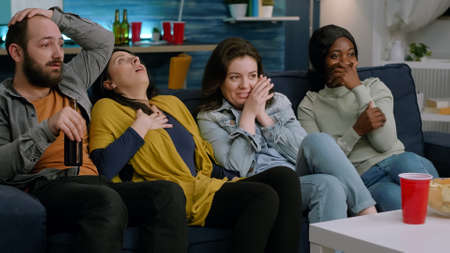 Group of multi-ethnic watching at terrifying movie on television sitting on sofa in apartment living room. Multi-racial friends having scary reaction spending time together late at night