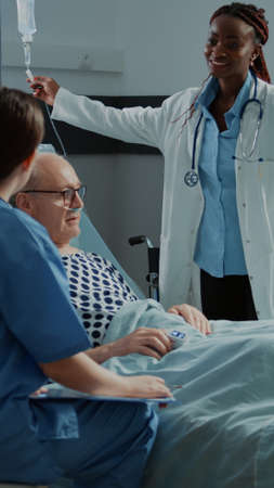 Multi ethnic medical staff checking patient healthcare problems to use healing treatment. Nurse and african american doctor tend to sick old man on bed in modern hospital ward