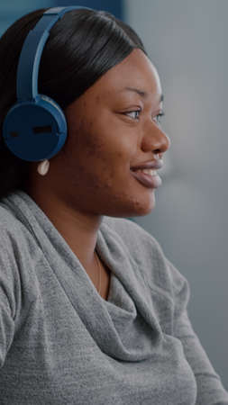 African american student putting headphone on head start listening relaxing music working remote from home sitting at desk in living room. Black woman browsing online course surfing on internt