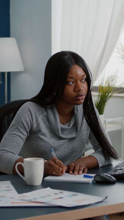 Black student drinking coffee while searching business information on internet using computer working at communication project. Focused woman sitting at desk in living room analyzing homework graphic