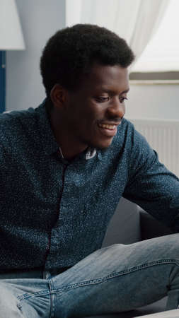 African american guy on online video call using phone in bright living room, internet online user working from home, connection with world for office communication and project planning
