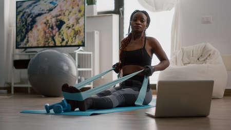 Fit black woman in sportswear looking at online workout on laptop working body muscle using fitness elastic enjoying healthy lifestyle. Athlete adult sitting on yoga map in living room
