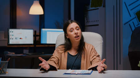 Pov of businesswoman discussing marketing project during online videocall meeting conference while sitting at desk in startup company office. Manager woman having business job interview late at night