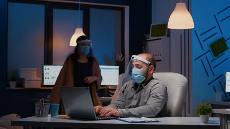 Workaholic businessman with face mask and visor against covid19 working in company office analysing marketing statistics on laptop. Manager remains alone in company room after his collegue left 写真素材