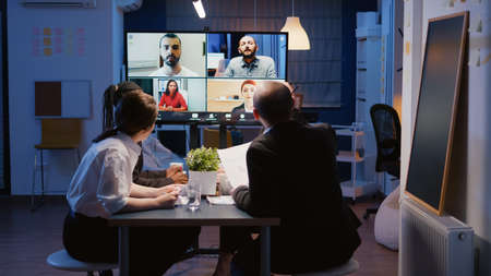 Multi ethnic businesspeople brainstorming company ideas during online videocall conference meeting discussing with remote teamwork. Diverse coworkers overworking in office room late at night