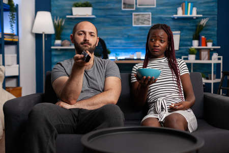 POV of interracial couple watching television and relaxing, looking at camera. Caucasian man using TV remote control to switch channels and african american woman holding popcorn snack