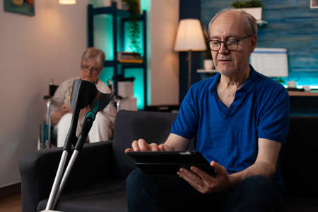 Couple of pensioners sitting at home with modern technology and healthcare support equipment. Caucasian man using digital tablet gadget on couch with crutches and woman in wheelchair