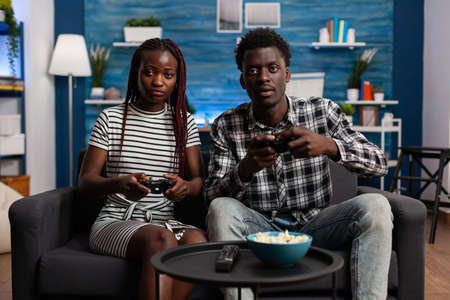 African american couple playing video game on TV console using controllers at television screen in living room. Black married people enjoying modern activity for fun and entertainment 写真素材