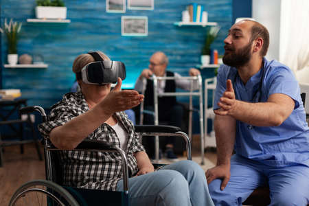 Male nurse giving social support, helping retired disabled senior woman to enjoy virtual reality using headset during caregiver service. Social nursing services at home. Healthcare assistance