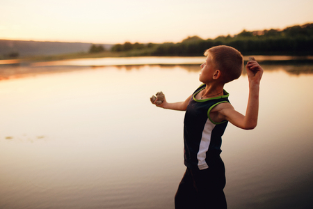 A young boy along on the lake and throw a stones into the water at sunset, summer holidays. Rural landscape. Horizontal outside shot.