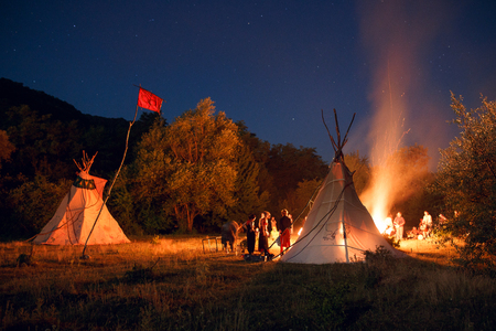 Camping with people in night forest with tipi and big bonfire on dark forest background. Horizontal outside shot.