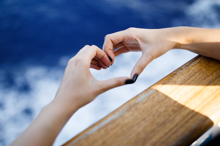 Mellow heart shaping female hands above sea waves.