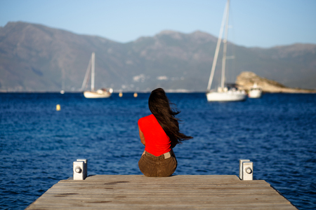 A lonely young brunette woman in red sitting with back on wooden pier, admiring seascape of the Corsica island, France. Mountains background. Horizontal view.
