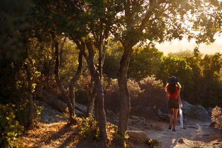 Eine junge Frau, die sich in der erstaunlichen Natur der Insel Korsika, Frankreich, zurücklehnt. Sonnenuntergang Hintergrund. Horizontale Ansicht. Standard-Bild