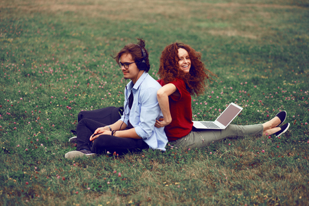 Two friends, sitting behind, using laptop and listening music in headphone, isolated on a green grass in open air. Leisure time. Фото со стока