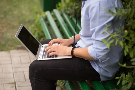 Cropped image of young man sitting at on the bench in the park, using a laptop and listening a music. Education concept, leisure.