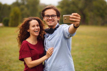 Two young smiling person, doing selfie in public park, isolated on a green grass in open air. Leisure time. Horizontal view.