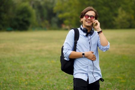 Young Caucasian Man Using Phone Outdoor. Фото со стока