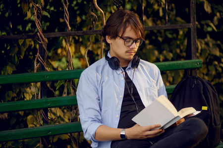 Portrait of a handsome young man in eyeglasses and headphones, read a book outside, isolated on a urban park background. Educational concept.