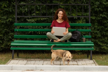 Attractive young woman sitting on a green bench in park and working with her laptop, beside a street pet, isolated outdoor on open air. Horizoontal view.