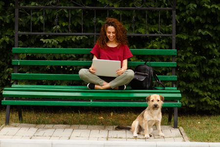 Image of a young woman sitting on a green bench in public park and working with her laptop, isolated outdoor on open air, beside sitting a little street dog. Horizoontal view.