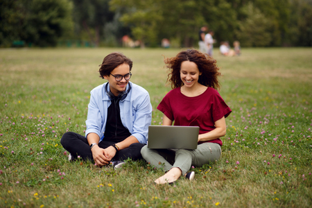 Two happy friends seated on a grass in urban park, using a laptop, isolated on a green grass forest background, beautiful day for works in open air. Communication, relationship,friendly concept. Фото со стока