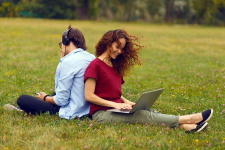 Image of a two young person, sitting behind, using laptop and listening music in headphone, isolated on a green grass in open air. Leisure time together. Horizontal view.