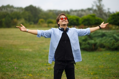 Happy youth boy with raised hands and red sunglasses sitting in park, feelings happiness. Freedom, emotional concept.