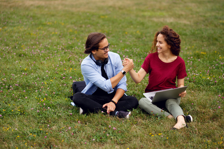 Portrait of a two friends seated on a grass in urban park, using a laptop and spend time together, high five, isolated green grass background, beautiful day for rest in open air.
