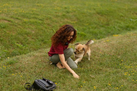 A woman seated on a green grass in the park playing with a street pet, isolated outdoor on open air. Horizontal view. Copy space.