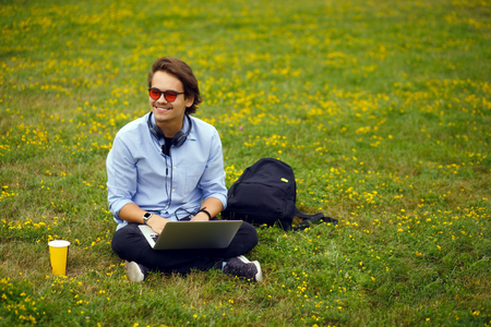 Image of young man seated on a green grass, using a his portable laptop and listening a music. Education concept, leisure. Copy space. Фото со стока