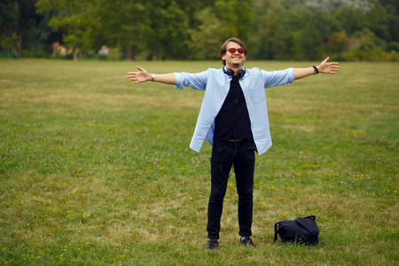 Portrait of a positive youth student with raised hands and red sunglasses sitting in park, feelings happiness, on a green grass background with copyspace. Фото со стока